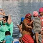 Sikh women helping there sons bathing in the golden temple (women had their own place to bathe)